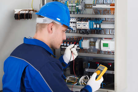 manual test equipment: Male Technician Examining Fusebox With Digital Insulation Resistance Tester Stock Photo
