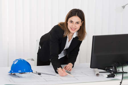 female architect: Young Happy Female Architect Working On Blueprint In Office
