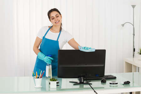 janitor: Happy Young Female Janitor Cleaning Computer With Rag