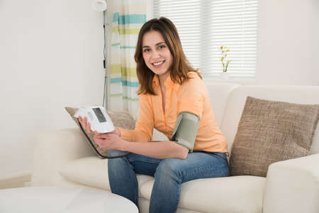 pressure: Smiling Woman Sitting On Sofa Measuring Blood Pressure