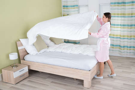 bedsheet: Young Female Housekeeper Changing Bedsheet On Bed In Room Stock Photo