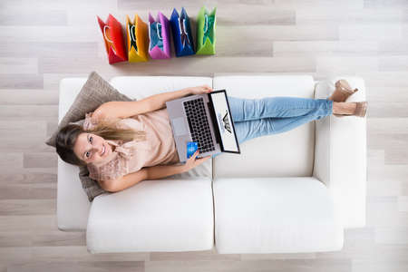 Young Woman Sitting On Sofa With Laptop Shopping Online 版權商用圖片 - 52812405