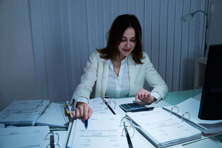 account executive: Happy Young Businesswoman Calculating Bill In Office