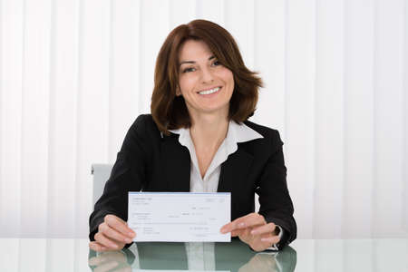compensate: Happy Businesswoman Offering Pay Cheque In Office Stock Photo