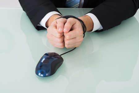 gefesselt: Close-up einer Person Handgelenk Bound By Computer-Maus-Kabel