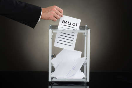 balloting: Close-up Of A Businessperson Hand Putting Ballot In Glass Box