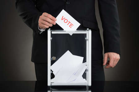 into: Close-up Of A Male Hand Putting Vote Into Ballot Box