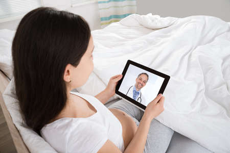 Pregnant Woman Talking To Doctor On Digital Tablet In Her Apartment Archivio Fotografico