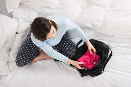bed clothes: Young Pregnant Woman Sitting On Bed Packing Baby Clothes Into Bag Stock Photo