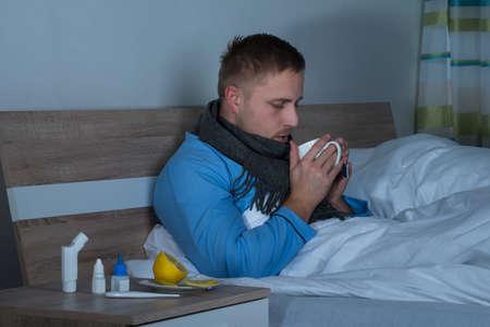 persona enferma: El hombre joven que se sienta en cama taza de té que bebe en su dormitorio Foto de archivo