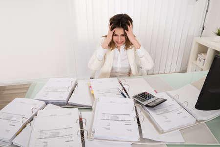 registros contables: Frustrado joven Contador sobrecargados de trabajo en la oficina