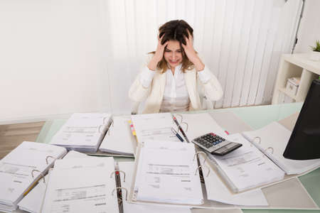 bank records: Frustrated Young Accountant Overloaded With Work In Office Stock Photo
