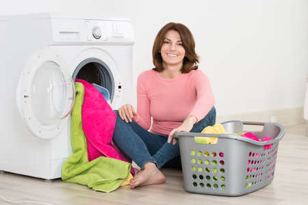washing machine: Happy Young Woman Putting Clothes Into Washing Machine At Home Stock Photo