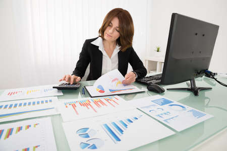 computer devices: Young Businesswoman Analyzing Report On Chart With Calculator Stock Photo