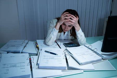 mujer decepcionada: Tensionada joven Trabajar hasta tarde en la oficina