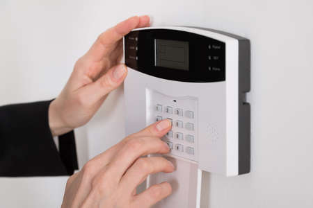 control panel: Close-up Of A Woman Hand Entering Code In Security System