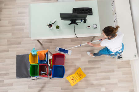 clean office: Young Female Janitor Mopping Wooden Floor With Caution Sign