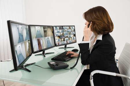 Operador de sexo femenino Mirando a la cámara múltiple de imágenes en computadoras mientras habla por teléfono
