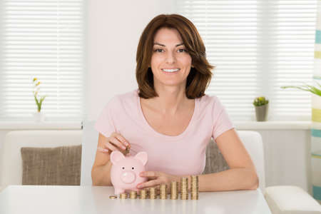 home security: Woman Inserting Coin In Piggybank In Front Of Stacked Coins Stock Photo