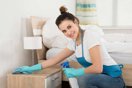 Happy Female Housekeeper Cleaning Nightstand In Room Foto de archivo