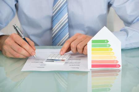 Close-up der Geschäftsmann Berechnung der Energieeffizienz Rate des Hauses in Büro