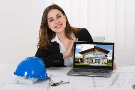 arquitecto: Arquitecto femenino que muestra la foto de la casa en la computadora portátil en la oficina