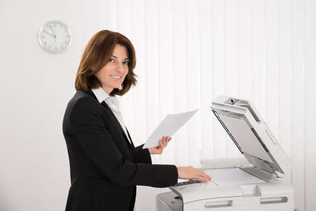 copying: Smiling Businesswoman Copying Paper On Photocopy Machine In Office