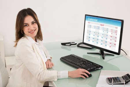 up to date: Happy Young Businesswoman Sitting In Office With Calendar On Computer At Desk