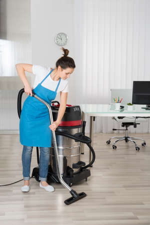 janitor: Female Janitor Cleaning Floor With Vacuum Cleaner In Office Stock Photo