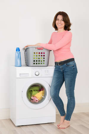 machine: Happy Young Woman Standing By Washing Machine With Detergent And Laundry At Home
