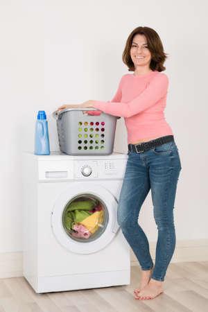 lavadora con ropa: Mujer feliz joven que se coloca por la lavadora con detergente y lavadero en el país