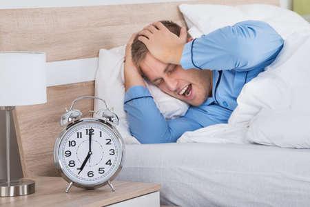 disturbed: Sleeping Man Disturbed By Ringing Alarm Clock After A Sleepless Night