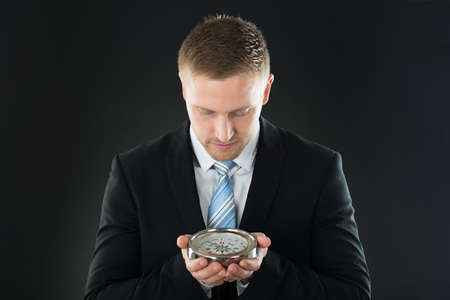 guiding: Portrait Of Young Businessman Holding Compass On Black Background Stock Photo