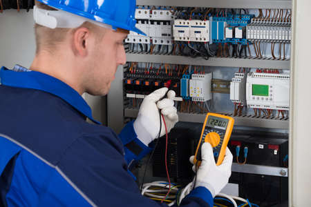 the tester: Male Technician Examining Fusebox With Digital Insulation Resistance Tester Stock Photo