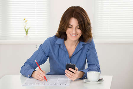classifieds: Young Woman Reading Classifieds On Newspaper With Smart Phone In Hand