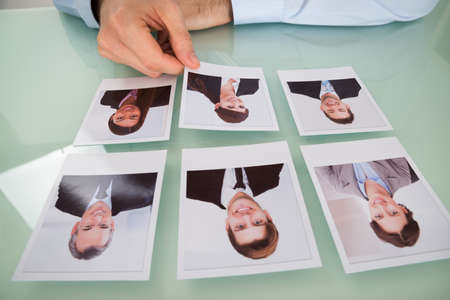 Close-up Of A Businessman Hand Choosing Photograph Of A Candidate photo