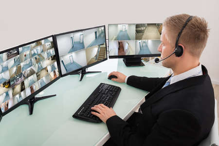 footage: Operator Looking At Multiple Camera Footage On Computer