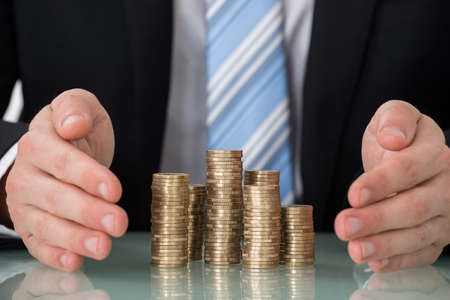 Close-up Of Businessperson Saving Pile Of Coins Stock Photo
