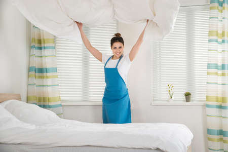 bedsheet: Happy Young Female Housekeeper Changing Bedsheet On Bed In Room