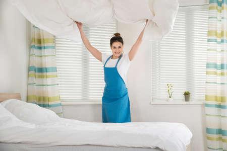 orden y limpieza: La hembra joven feliz ama de casa Cambio Bedsheet en cama en sitio