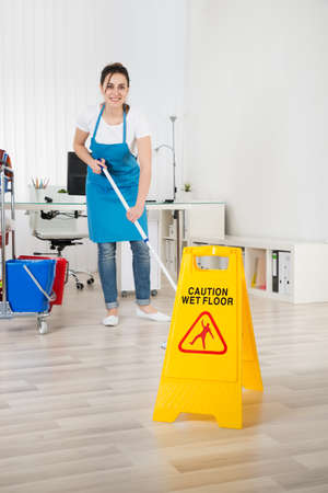 janitor: Female Janitor Mopping Wooden Floor With Caution Sign
