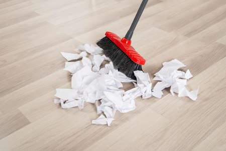 brooming: Broom With Torn White Papers On Hardwood Floor Stock Photo