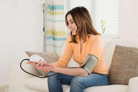Smiling Woman Sitting On Sofa Measuring Blood Pressure