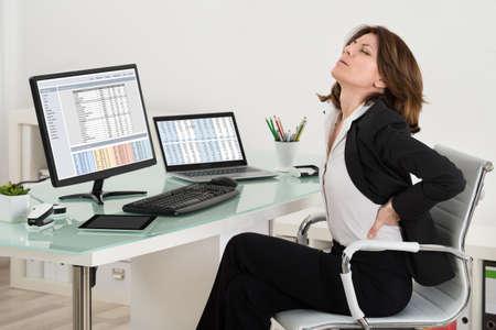 Empresaria que sufre de dolor de espalda mientras trabajaba en la oficina
