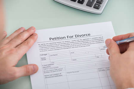 dissolution: Close-up Of Person Hand Over Petition For Divorce Form Stock Photo