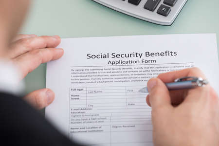 Primer plano mano de la persona de llenado de la Seguridad Social Beneficios Formulario Foto de archivo - 52952169
