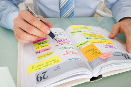 event planner: Close-up Of A Businessman Writing Note In Diary