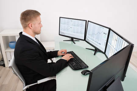 multiple: Young Businessman Looking At Graph On Multiple Computer Screen