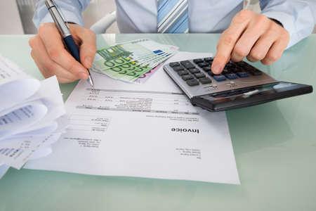 デスクでユーロ紙幣と請求書を計算する実業家のクローズ アップ