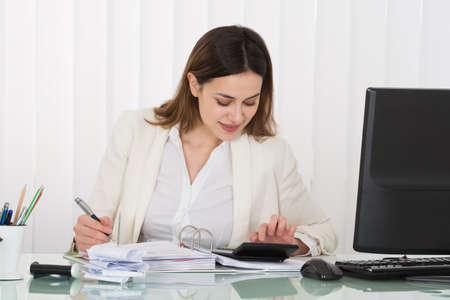 Photo Of Happy Businesswoman Calculating Bills In Office 写真素材